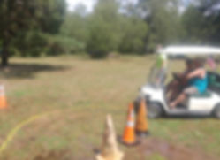 a golf cart drivin through an obsticle course by a blind folded person