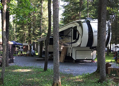 A camper in a camp site that has water, sewer, and 50 amp electric