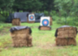an archery range with targets on bails of hay