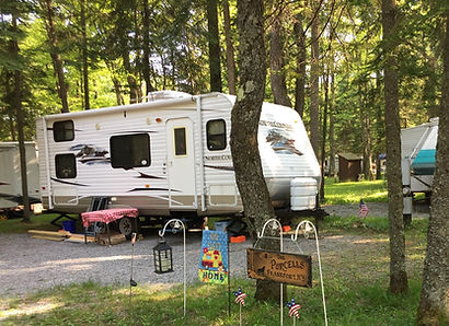 A camper in a camp site that has water and 50 amp electric