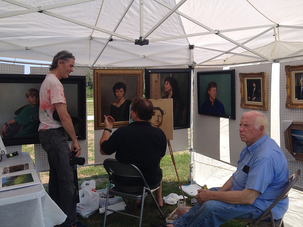 High school students watch Bill demonstrating painting a portrait of Omar from a photo.