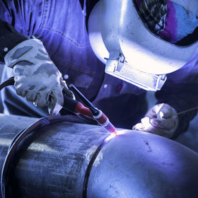 Worker welding metal piping using tig we
