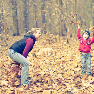 Little boy throwing up leaves with his mother in forrest