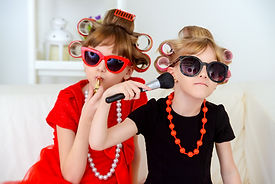 Two funny little girls with curlers in t