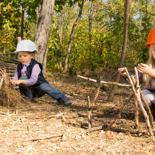 Two young children pretending to be builders or construction workers wearing hardhats and