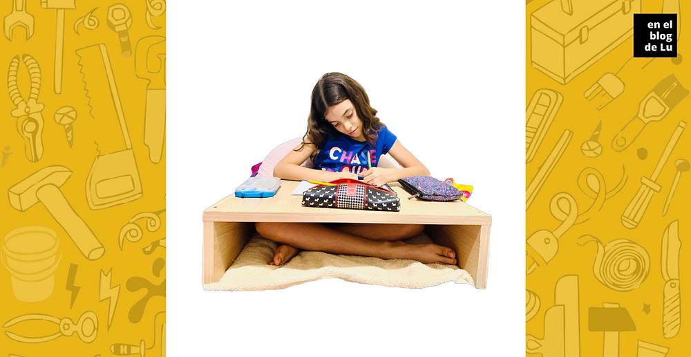 niña sentada usando mesa para la cama