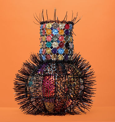 An innovative vessel by contemporary basketry artist Emily Dvorin, crafted from coffee pods, metal hardware, wire, brass rings, and cable ties.