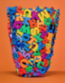 A contemporary sculptural  basket created from magnetic letters by sculptural basketry artist, Emily Dvorin.