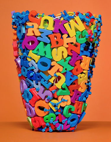 A contemporary sculptural  basket created from magnetic letters by sculptural basketry artist Emily Dvorin.