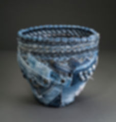 A contemporary vessel by Sausalito basket artist, Emily Dvorin, made from denim jeans seams & other parts, threads, and cable ties.