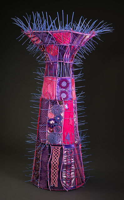 A contemporary vessel by Sausalito basket artist, Emily Dvorin, made from tomato cage, fabric, plastic, zippers, embroidery floss, pencils, needlepoint canvas, buttons, and cable ties.