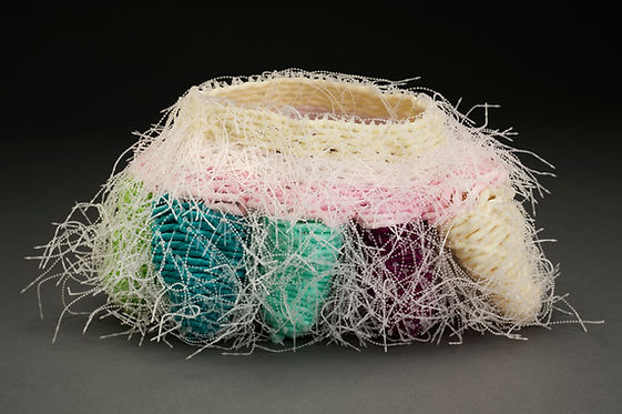 A contemporary vessel by Sausalito basket artist, Emily Dvorin, made from deconstructed mesh bath poofs and security ties.