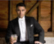 Guy intuxedo with white bow tie with drink