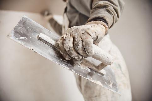 Workman plastering gypsum walls inside t