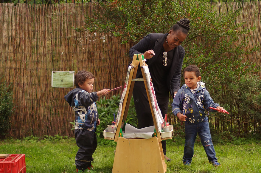 Joan and children painting at the WPCA nursery