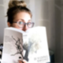 Author Katrina D Hamel wearing glasses and messy bun looking over edge of paperback book 'Dividing Sword'