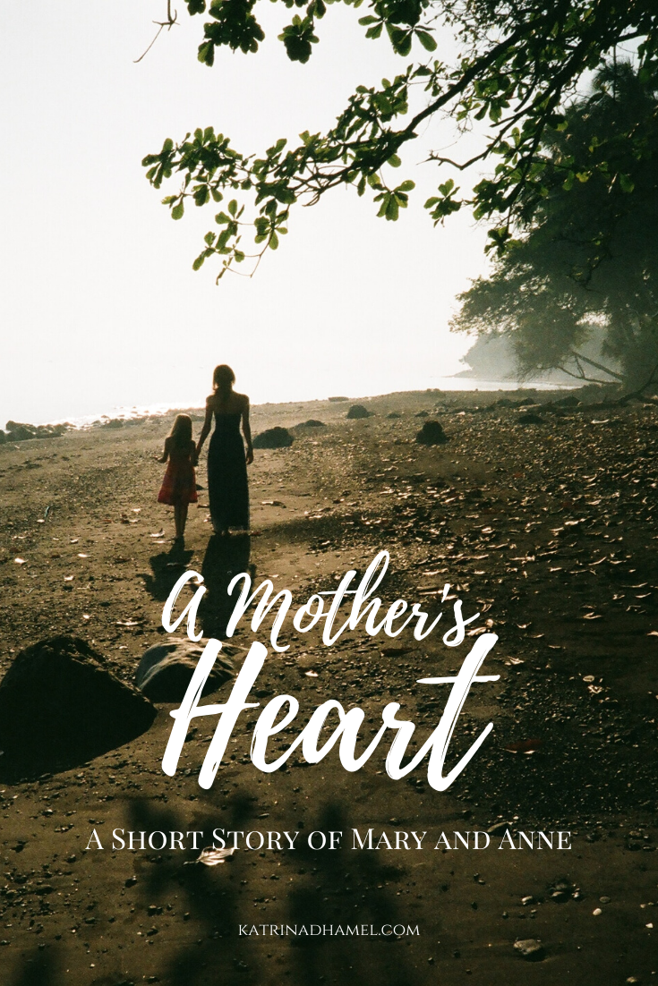 Mother and young daughter walk together on a pebbly path near water and the text 'A Mother's Heart, A Short Story of Mary and Anne'