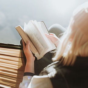 looking over the shoulder of a blonde woman reading bible