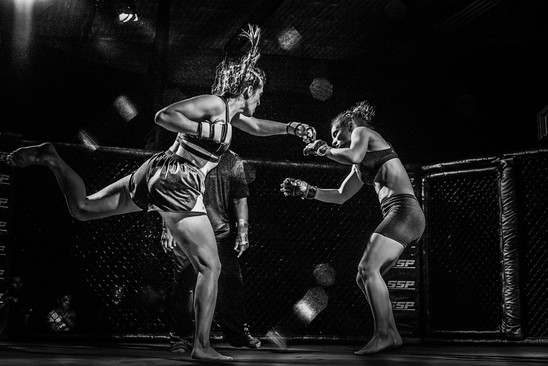 Bonnie Von Duyke (Chase) superman punches Shannon Murray (Nora) while fighting in the octagon