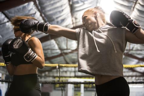 Shannon Murray (Nora) punches Roxana Sanchez (Aisha) while training