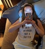 """Karen wearing a white t-shirt that says """"I'm a warrior not a quitter"""". She is laying in bed, while looking at her phone."""