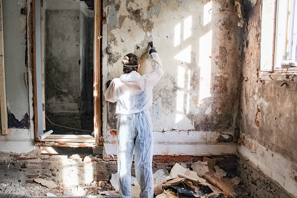Girl scratching wallpaper off the wall in an old house with a protection jumpsuit