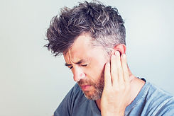 Man with earache is holding his aching e