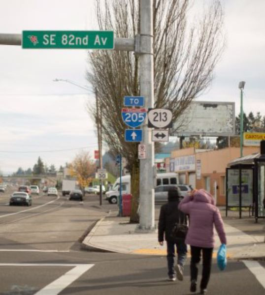 """People cross a large city street under signs that read """"SE 82nd Av"""" and """"to I -205"""""""
