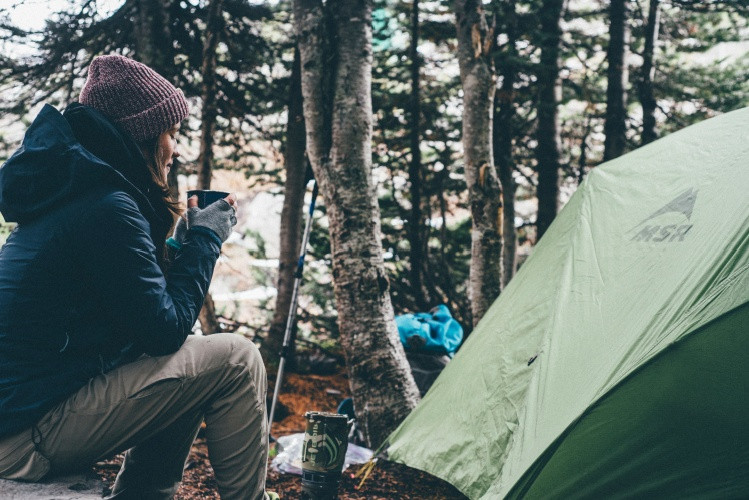A woman with her hiking gear, next to a tent drinking coffee and enjoying the outdoors