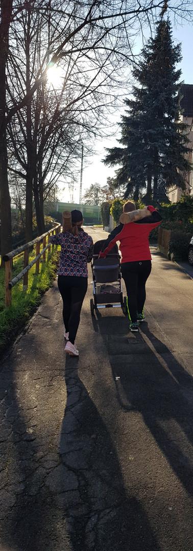Manu und Niki mit Kinderwagen Baumstamm auf der Schulter