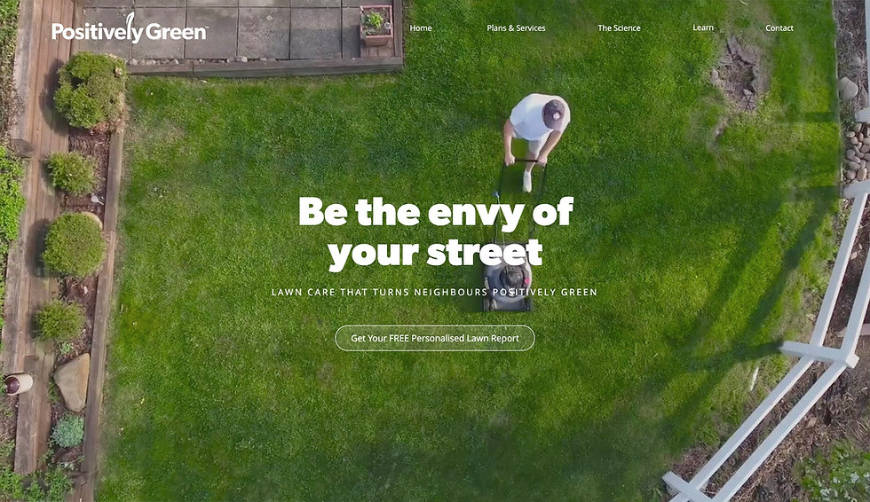 Website thumbnail for Positively Green. Background is a downward perspective of a man mowing the lawn in a green garden. In the center of the image is bold white text, Below this text is smaller body text and below this is a button containing small white text on a faded background. On the top right is a menu bar and on the top left is a brand name in white text.
