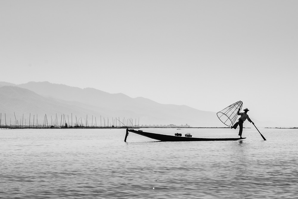 a face fisher man acting like he is catching some fish Inle Lake Myanmar
