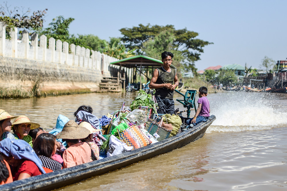 long boat crowded with people and groceries at Inle Lake Myanmar