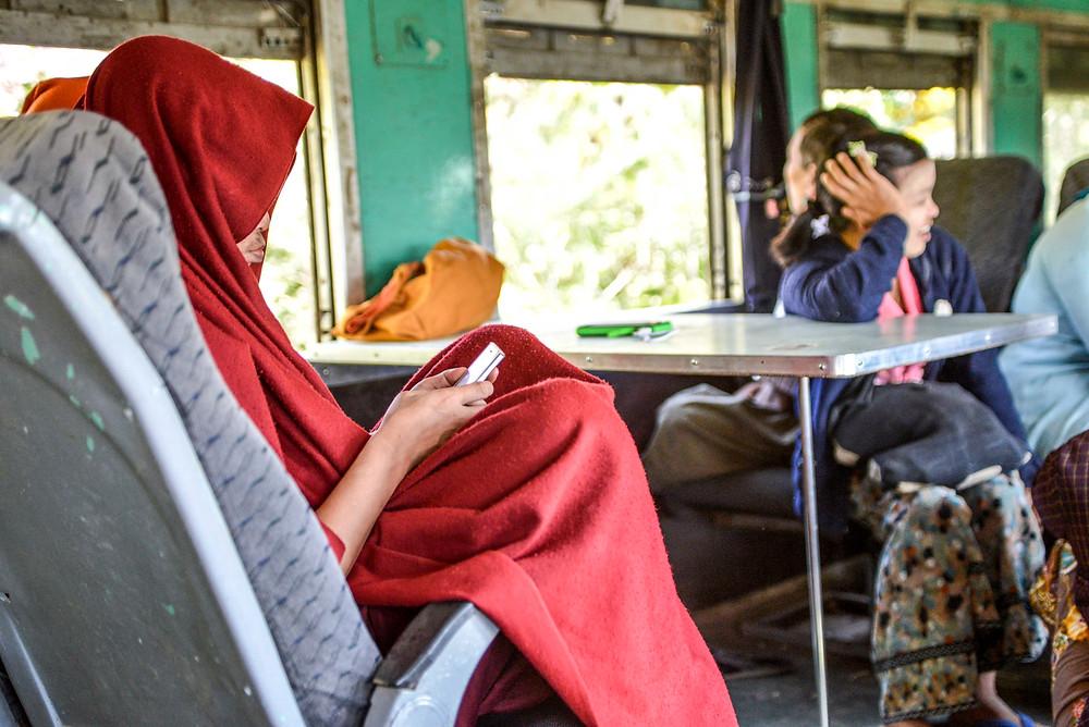 Mönch spielt auf seinem Weg im Zugabteil. Myanmar.