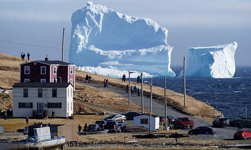 Photo of an iceberg nearby the shore with a dozen people looking at it