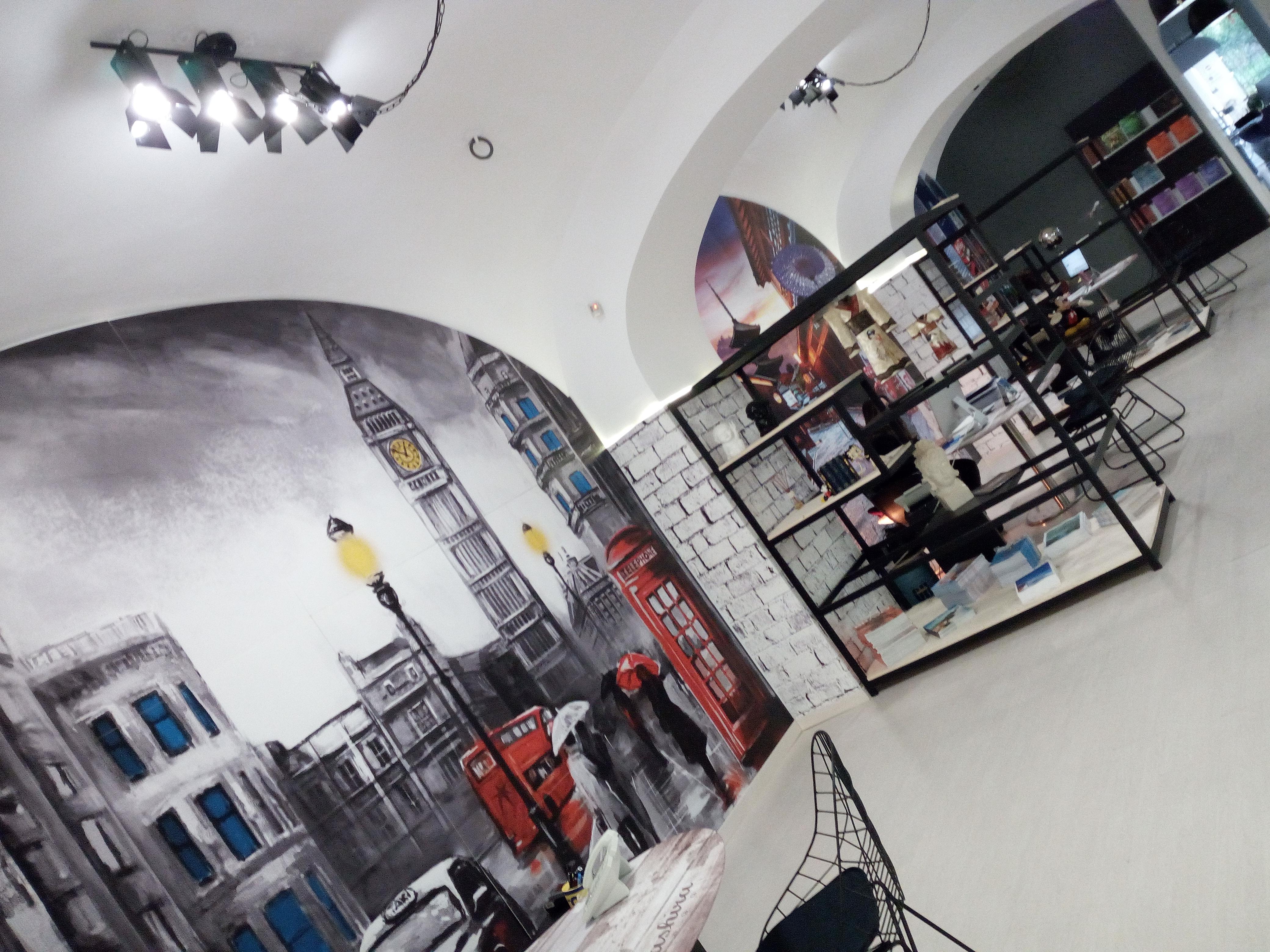 Progettazione e allestimento agenzia di servizi, parete decorata, scaffali su misura