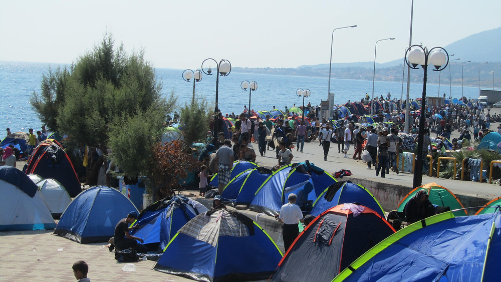 Tents in the foreground and refugees in the background