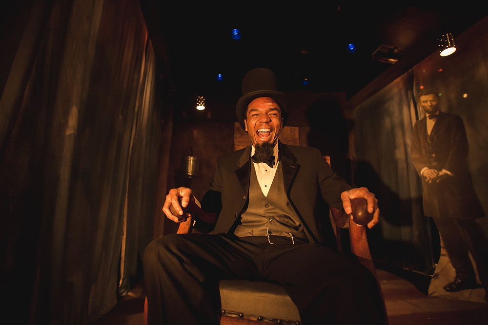 A Black man dressed as Lincoln laughs to the camera.
