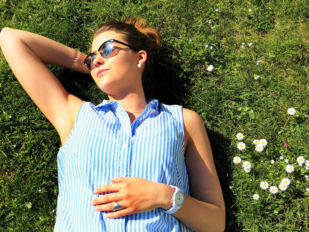 A girl laying on the grass in the sun.