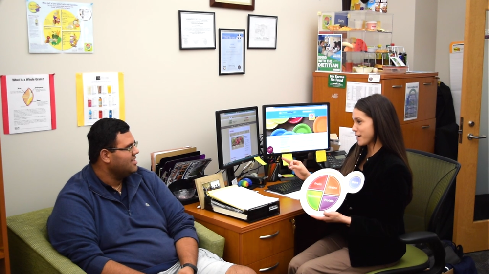 A dietitian shoing a client the MyPlate explaining portion sizes and nutrients.