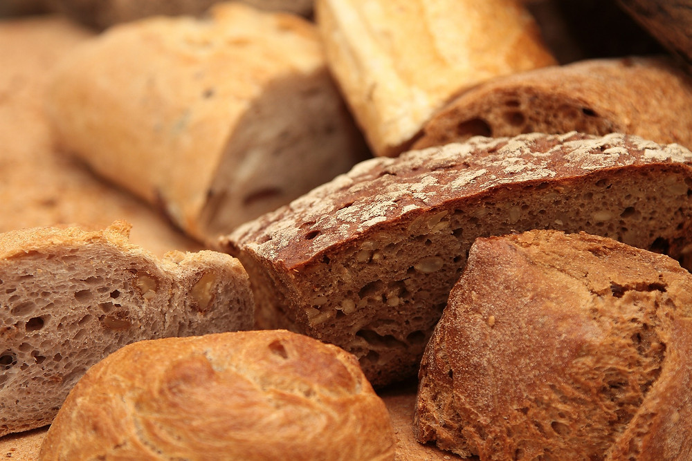 A bunch of different types of loaf's of bread.