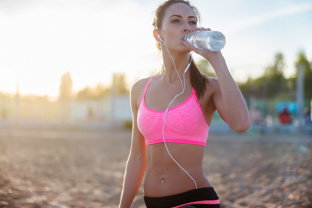 A girl on the beach on a run drinking water.