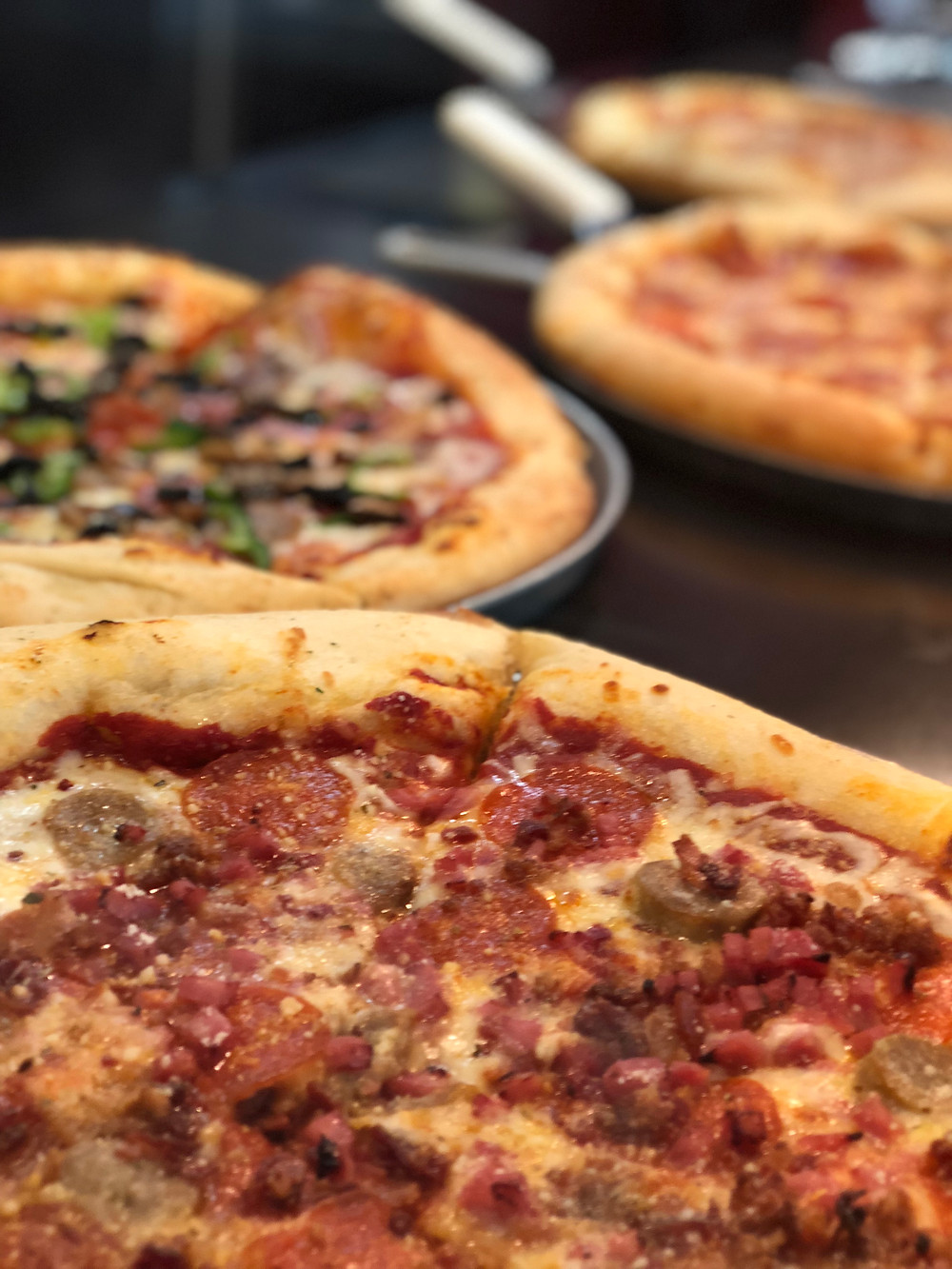 Close up of many different pizzas.