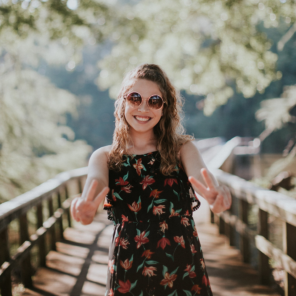 Girl with sunglasses on wooden bridge smiling and throwing up peace signs with both hands
