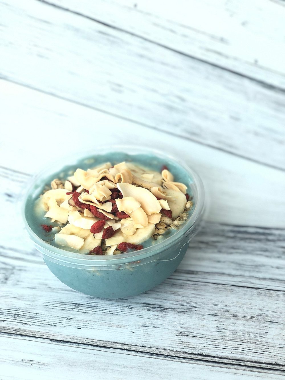 A smoothie bowl topped with banana, goji berries, and coconut flakes.