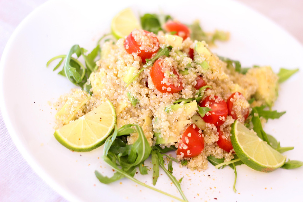A couscous salad with arugula and tomatoes.