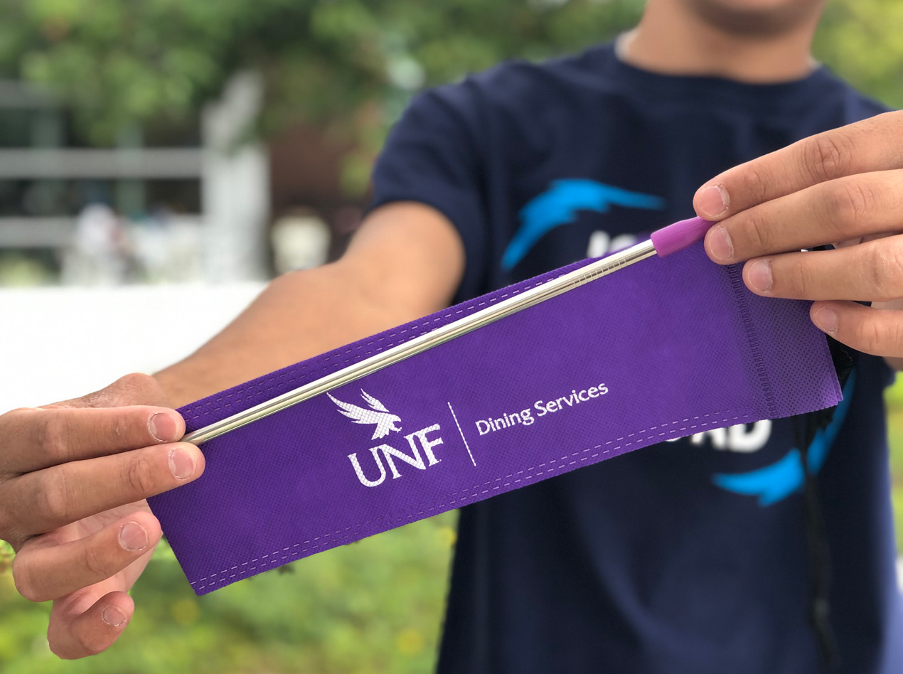 Guy holding purple metal straw with UNF dining logo