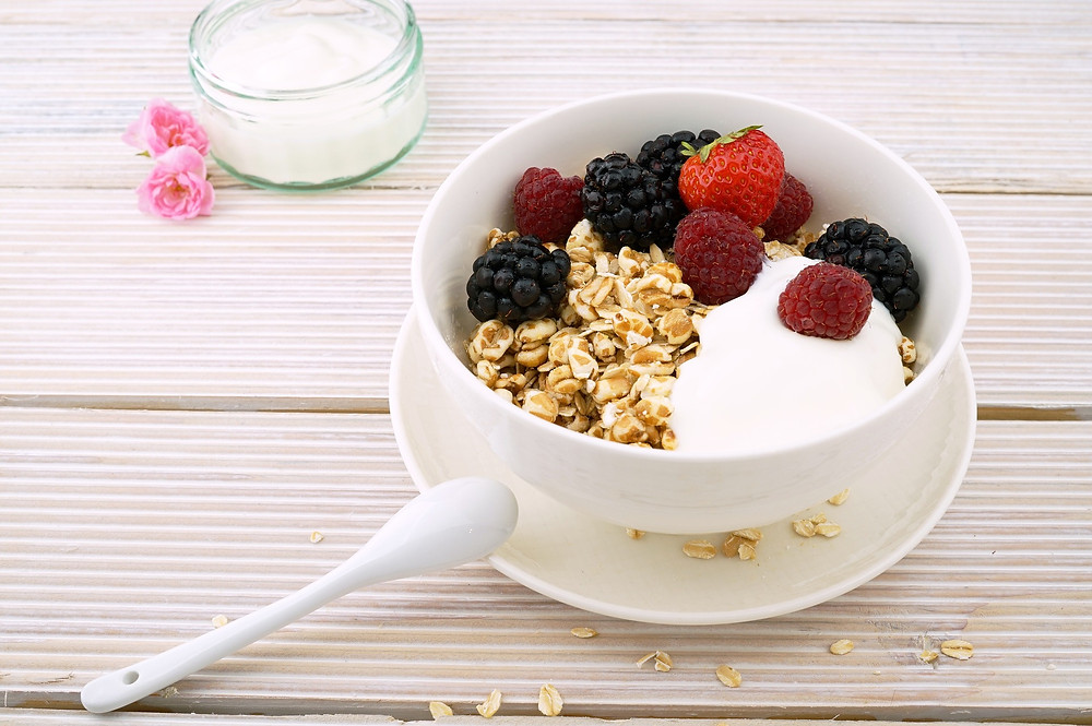 A bowl of yogurt, granola, and berries.