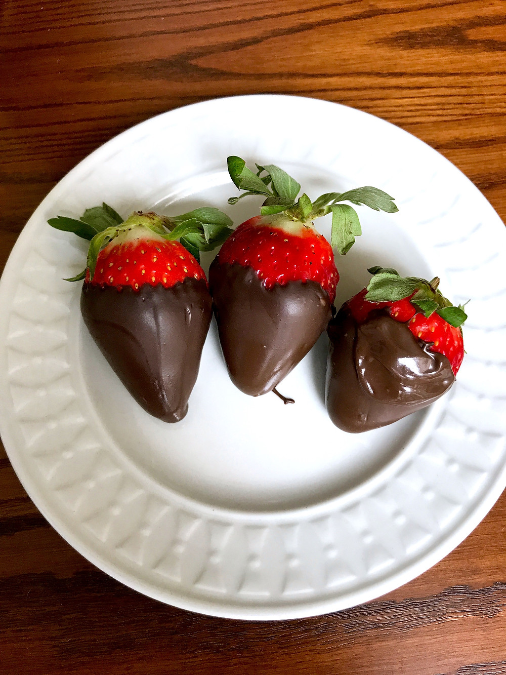 A plate of three chocolate covered strawberries.