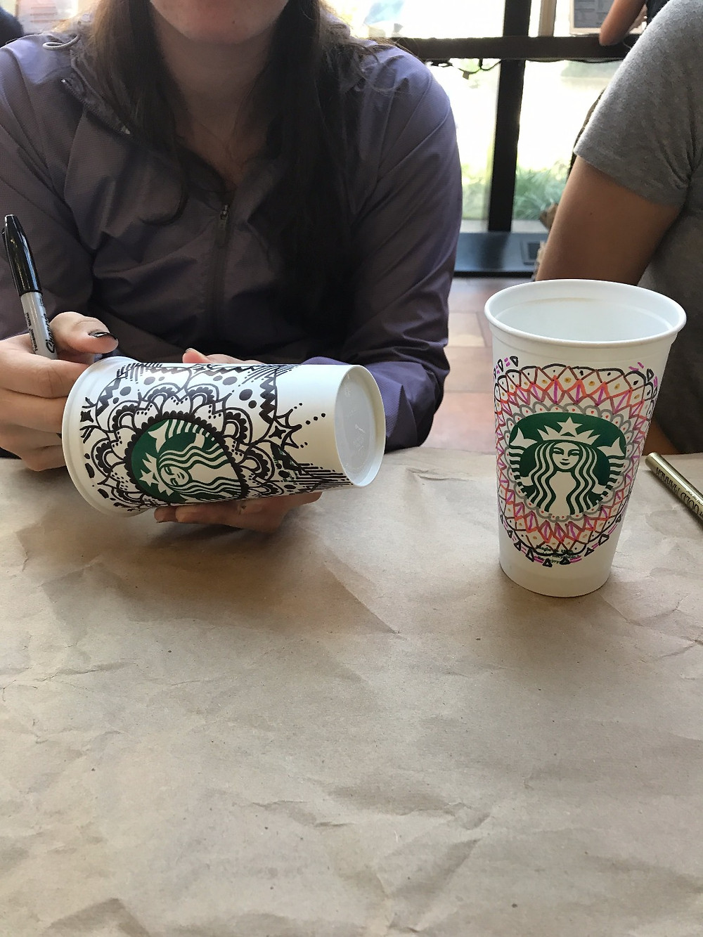 A close up view of two Starbucks cups that were decorated.